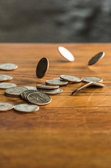 As moedas de prata e ouro e moedas caindo no fundo de madeira