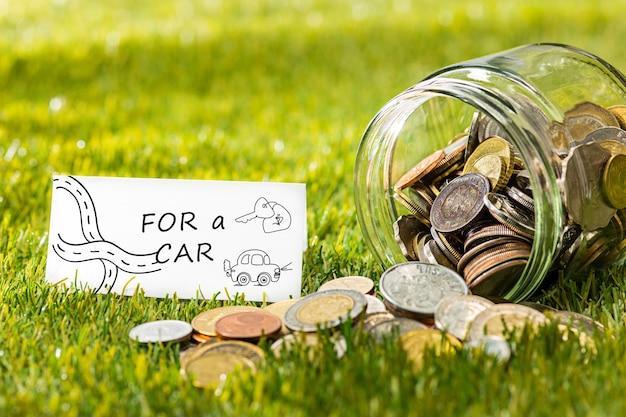 As moedas em frasco de vidro por dinheiro contra a grama verde. conceito financeiro de poupança e investimento