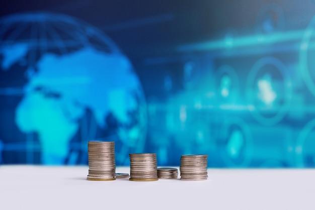 As moedas empilhadas com um logotipo de dinheiro do mundo na parte de trás.