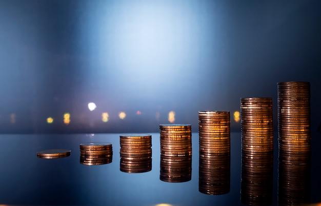 As moedas empilham o crescimento para o conceito da finança e do negócio, conceito de salvamento do dinheiro.