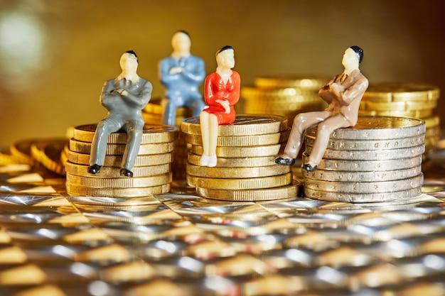 As moedas estão empilhadas umas sobre as outras com as figuras de empresários sentados sobre elas - uma crise de mercado e um mercado frágil