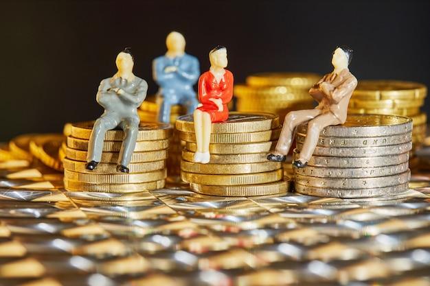 As moedas estão empilhadas umas sobre as outras com as figuras de empresários sentados sobre elas
