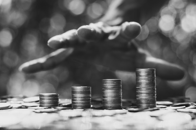 As moedas estavam empilhadas quatro em uma fileira e havia a mão de um homem, um empresário, prestes a agarrar.