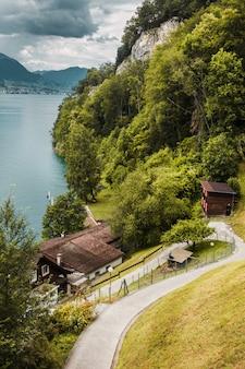As montanhas da floresta aconchegam a estrada e as casas tradicionais de um vilarejo suíço no fundo do lago lucerna