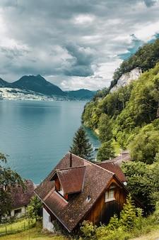As montanhas da floresta aconchegam as casas de vilarejos suíços tradicionais ao fundo do lago lucerna