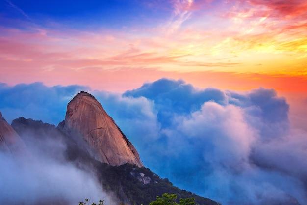 As montanhas de bukhansan estão cobertas pela névoa matinal e o nascer do sol no parque nacional de bukhansan, em seul, na coreia do sul