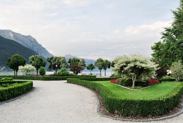 As montanhas, o lago e o aterro da cidade com árvores aparadas, arbustos, gramados e canteiros de flores.