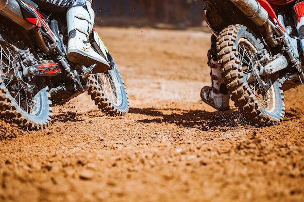 As motos de montanha correm em pista de terra com restos voadores durante uma aceleração