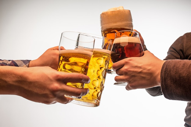 As muitas mãos masculinas com canecas de cerveja brindando isoladas no fundo branco do estúdio. esporte, fã, bar, pub, celebração, conceito de futebol futebol.