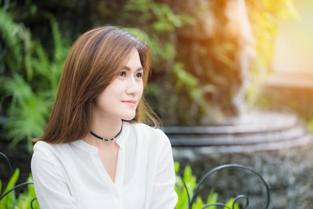 As mulheres adultas asiáticas únicas de portait sorriem no parque apreciam a vida boa e o conceito saudáveis do estilo de vida