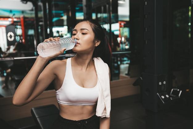 As mulheres após o exercício bebem água de garrafas e lenços no ginásio.