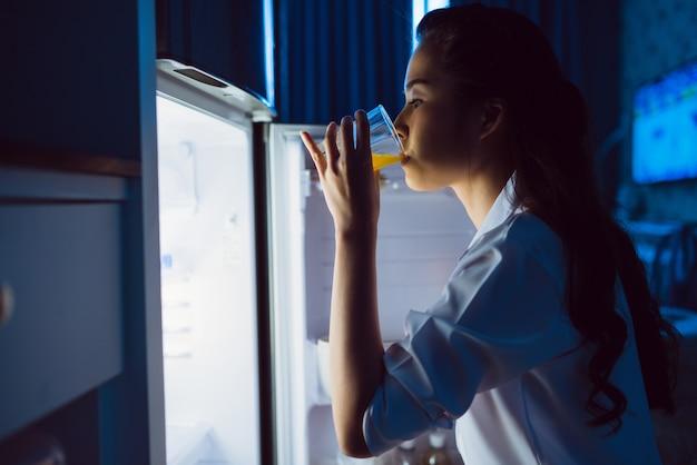 As mulheres asiáticas abrem a geladeira, bebem suco de laranja à noite.