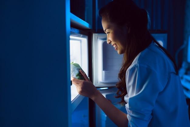 As mulheres asiáticas abrem a geladeira, comem a sobremesa à noite.