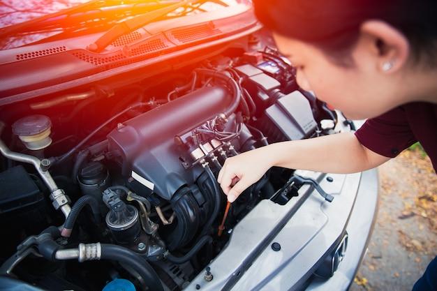 As mulheres asiáticas auto nível de óleo do motor do carro check-up antes de ir viagem