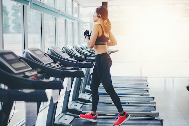 As mulheres asiáticas correndo sapatas do esporte no ginásio e mulher está tendo jogging na esteira
