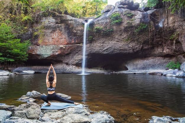 As mulheres asiáticas da moça estão jogando a ioga na frente da cachoeira.
