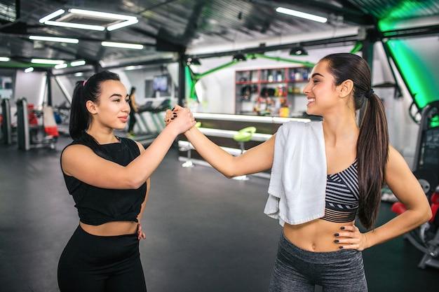As mulheres asiáticas e europeias novas estão na frente uma da outra e mantêm as mãos unidas.