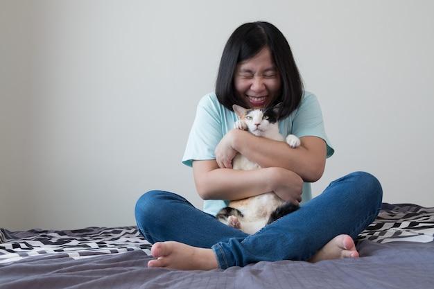 As mulheres asiáticas estão abraçando amorosamente gatos gordos.
