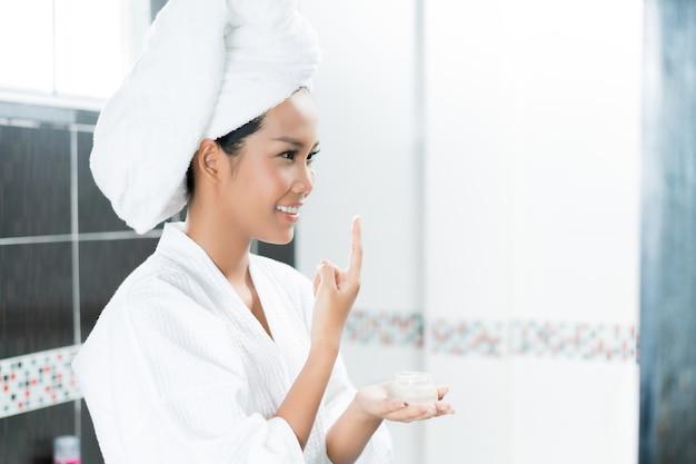 As mulheres asiáticas estão aplicando creme e loção para o rosto depois de tomar banho no banheiro.