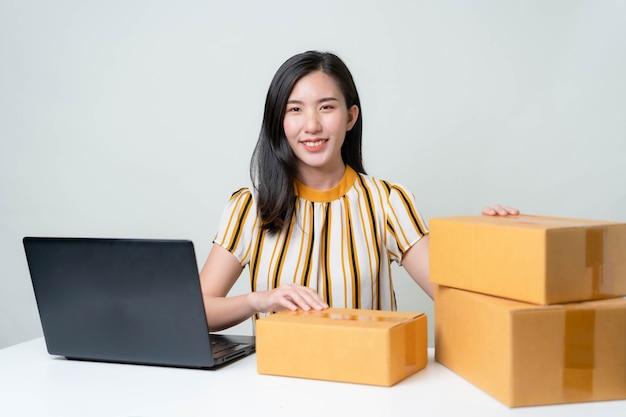As mulheres asiáticas estão começando um novo negócio no mercado online. mulheres asiáticas verificando produtos, preparando-se para entregar produtos aos clientes. conceito pme Foto Premium