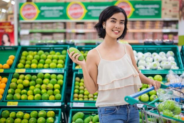 As mulheres asiáticas estão comprando frutas e legumes do supermercado.