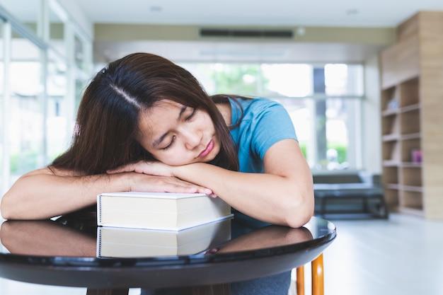As mulheres asiáticas estão dormindo depois de ler livros na biblioteca