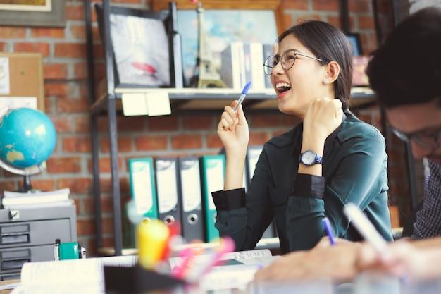 As mulheres asiáticas estão felizes por ela pensar no trabalho.