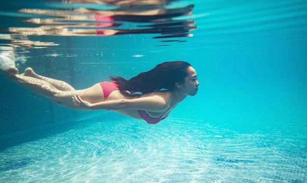 As mulheres asiáticas estão mergulhando na piscina.