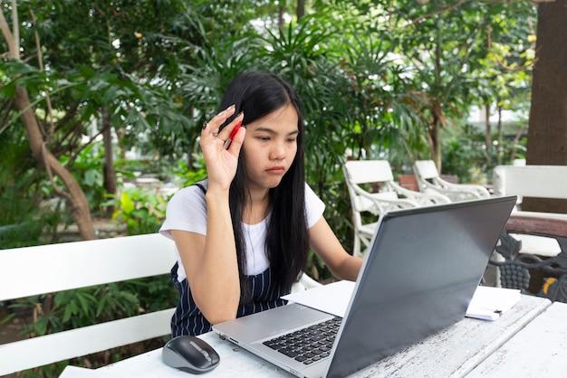 As mulheres asiáticas estão pensando tarefa com o laptop. ela sentada no parque na mesa branca.