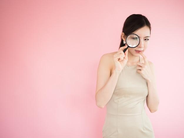 As mulheres asiáticas estão procurando por algo através de uma lupa e tocar sua boca
