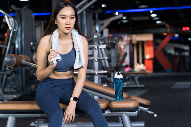As mulheres asiáticas estão sentadas no exercício e estão segurando toalhas com garrafas de água colocadas de lado