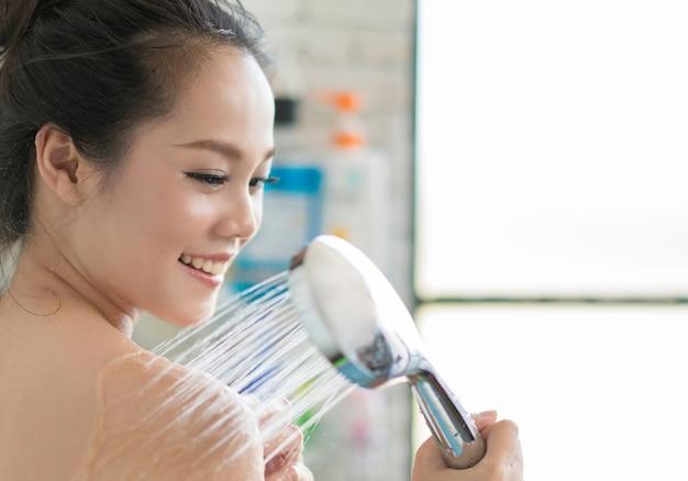 As mulheres asiáticas estão tomando banho no banheiro, ela está esfregando sabão, ela está feliz e relaxada.
