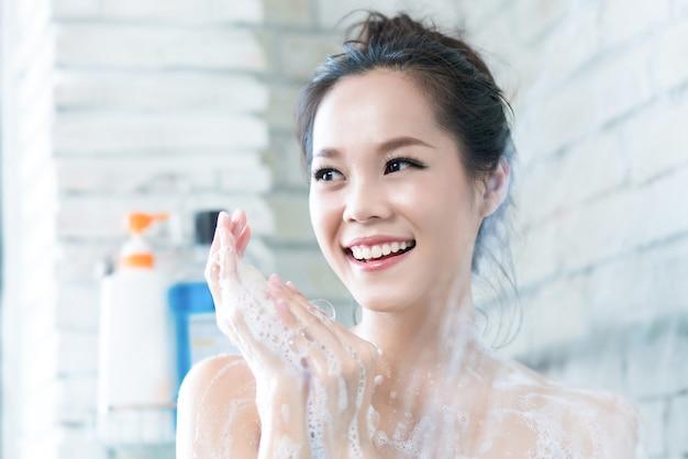 As mulheres asiáticas estão tomando banho no banheiro ela está esfregando sabão, ela está feliz e relaxar