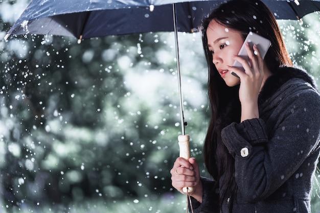 As mulheres asiáticas estão usando guarda-chuvas, a chuva está caindo. ela está chamando