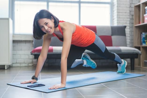 As mulheres asiáticas exercem indoor em casa ela é atuada
