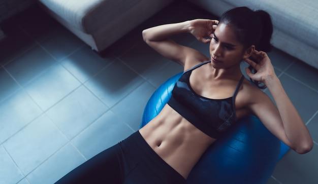 As mulheres asiáticas exercitam em casa.suas flexões na bola.