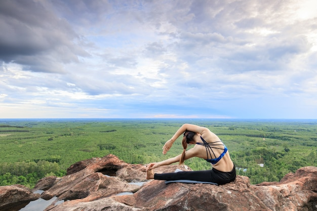 As mulheres asiáticas jogam-no ioga no penhasco da rocha da montanha.