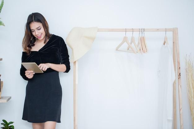As mulheres asiáticas jovens tocam no tablet do telefone inteligente para fazer compras e pedir itens para os negócios dela,