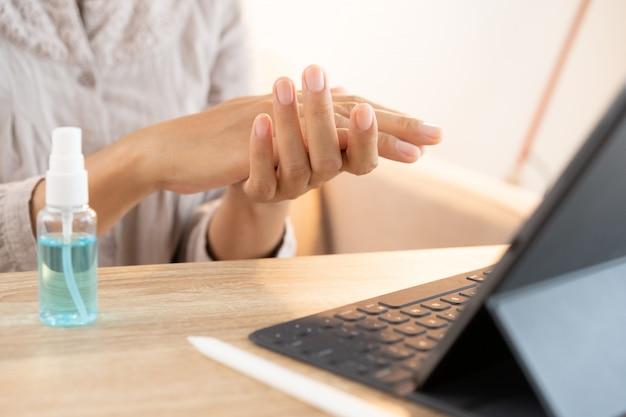As mulheres asiáticas limpe a mão com spray desinfetante de álcool, evite a propagação de germes e bactérias e evite o vírus covid-19