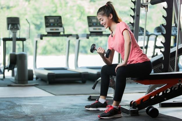 As mulheres asiáticas malham levantando um peso no gym.