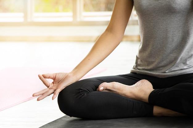 As mulheres asiáticas meditam enquanto praticam ioga, conceitos independentes, relaxando a felicidade das mulheres, a calma, o pano de fundo da sala branca.