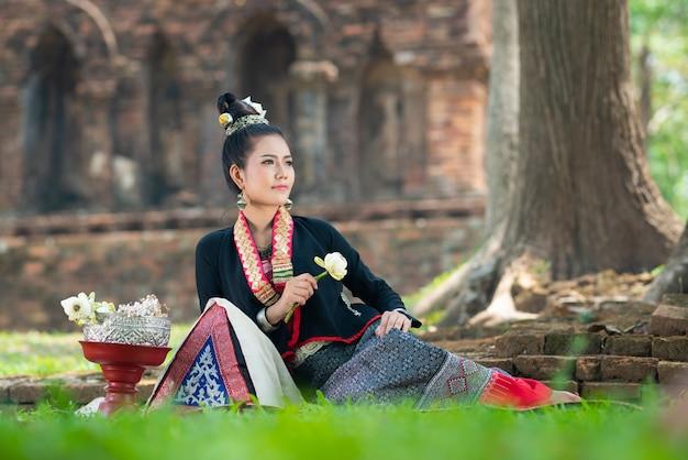 As mulheres asiáticas novas no vestido tradicional sentam-se na grama verde com a mão do descanso guardam lótus brancos. meninas bonitas no traje tradicional menina tailandesa no vestido tailandês retro.