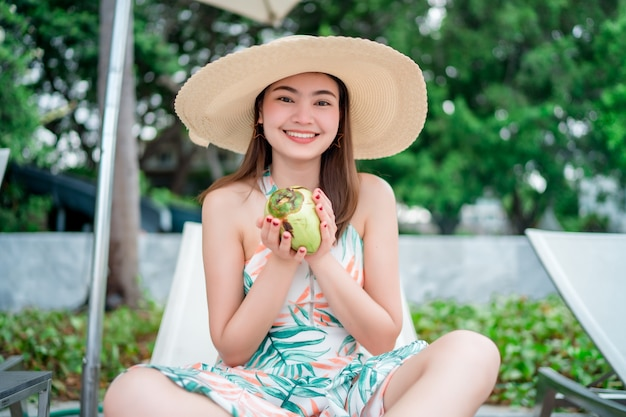 As mulheres asiáticas o turista ela está sentada relaxar na praia