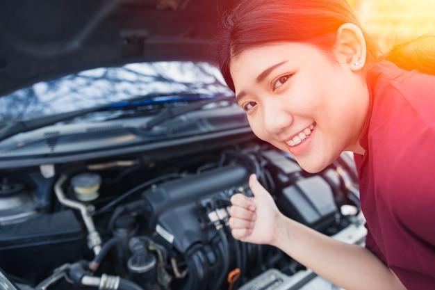 As mulheres asiáticas polegares para cima bom motor de carro check-up antes de ir viagem