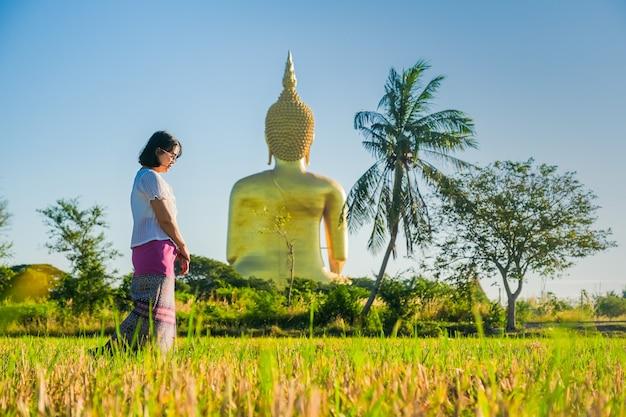 As mulheres asiáticas que andam e que andam meditam o templo no gramado atrás de uma imagem dourada de buddha.