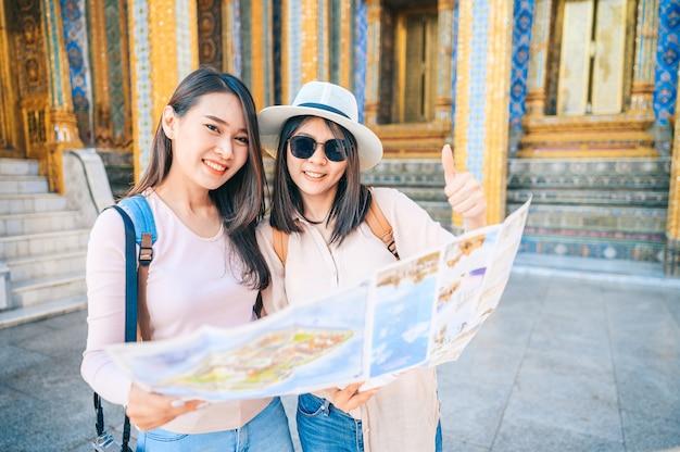 As mulheres asiáticas que dão os polegares acima do sinal da mão viajam no templo da esmeralda buddha, tailândia