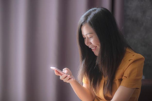 As mulheres asiáticas que jogam jogos móveis no interior sorriso feliz