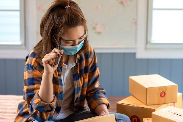 As mulheres asiáticas que trabalham sentam e pensam sobre a análise de mercado da casa no assoalho da sala com o pacote postal, vendendo o conceito em linha das ideias, normal novo.
