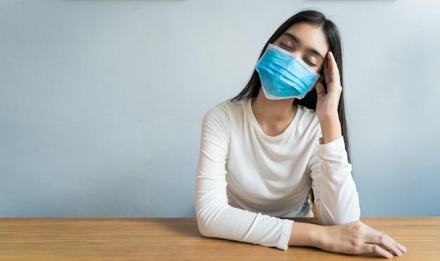 As mulheres asiáticas que usam máscara estão segurando a cabeça por causa de dores de cabeça. ela tem febre e enxaqueca por causa do estresse ou dorme tarde, pouco sono, descanso insuficiente no conceito saudável, com espaço para texto.