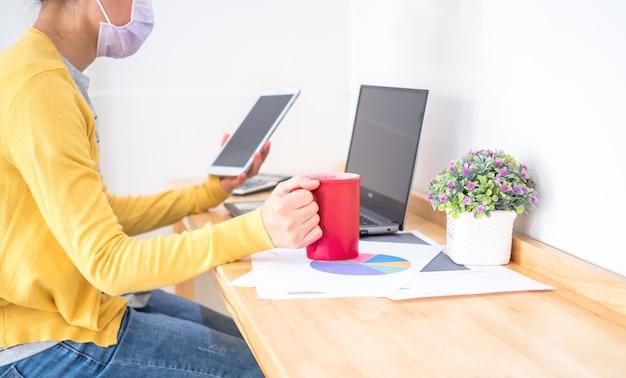 As mulheres asiáticas que usam máscaras trabalham em casa, usando o notebook e o tablet e segurando a xícara de café. reduzir a disseminação do coronavírus durante a crise do covid-19. trabalhar em casa e conceito de saúde.